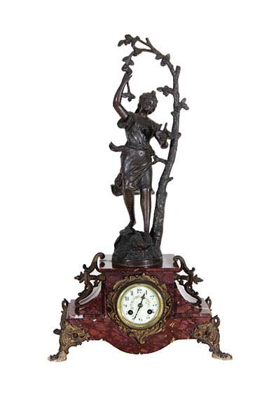 A marble table clock with brass ornament and bronze statue on top